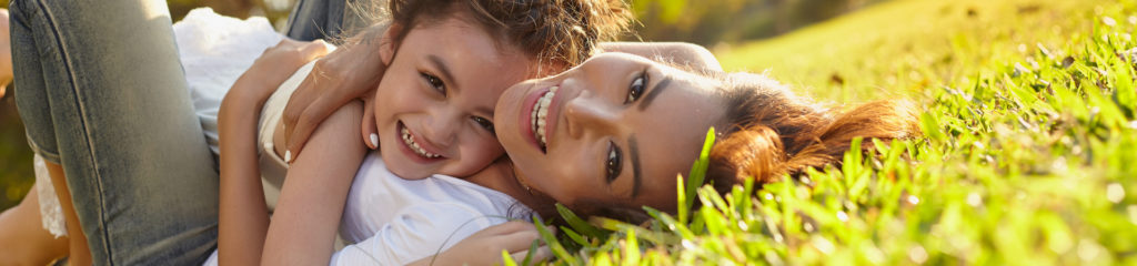 mother and daughter smiling in grass