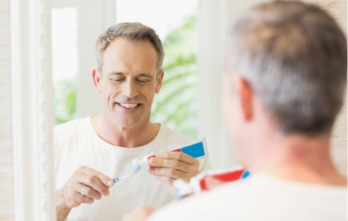 man in bathroom putting toothpaste on a toothbrush