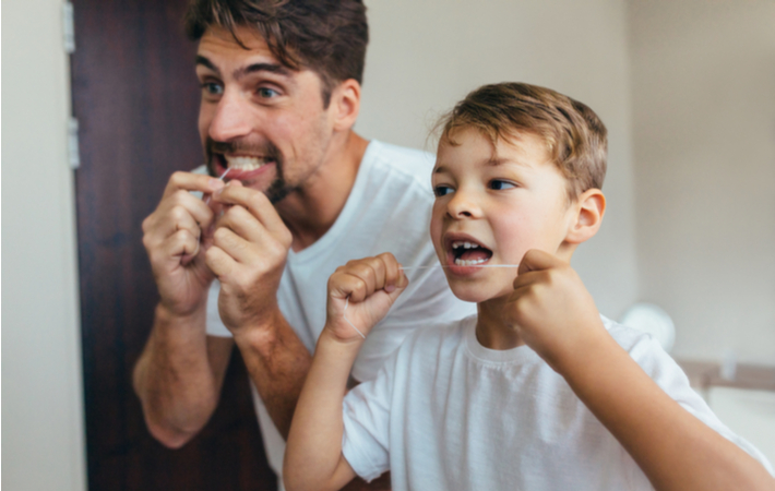 father and son flossing together in the bathroom
