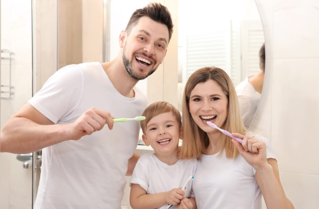 smiling family with healthy teeth brushing their teeth together