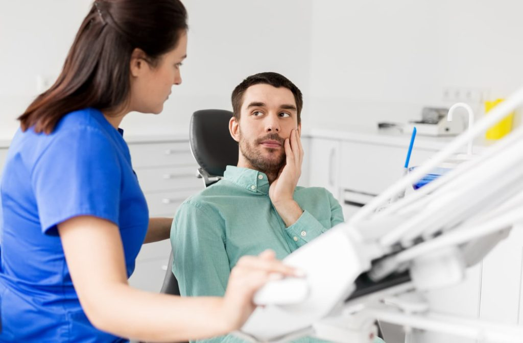 Dental patient holding his jaw and talking to his dentist about TMJ pain
