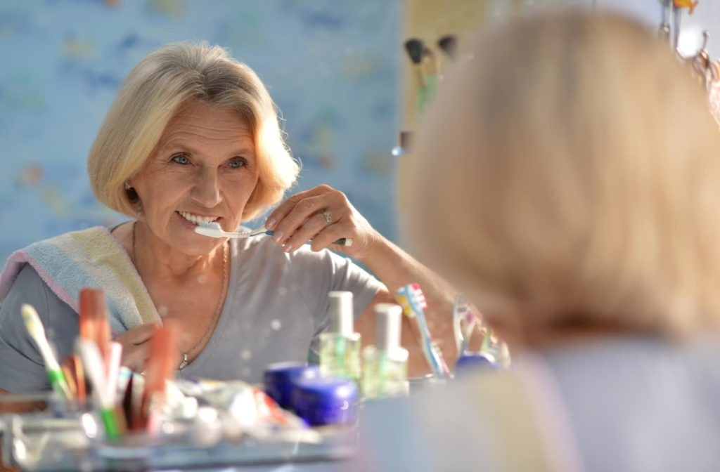 Senior woman smiling and looking in the mirror while brushing her teeth
