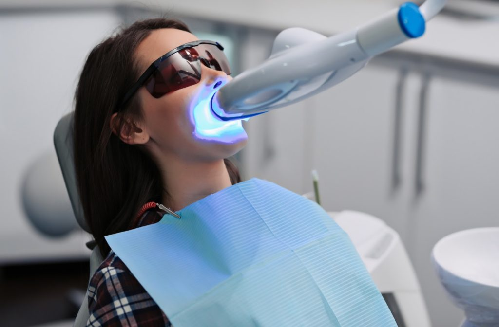 Woman in dentist's chair wearing protective glasses and getting a bleaching procedure activated by light
