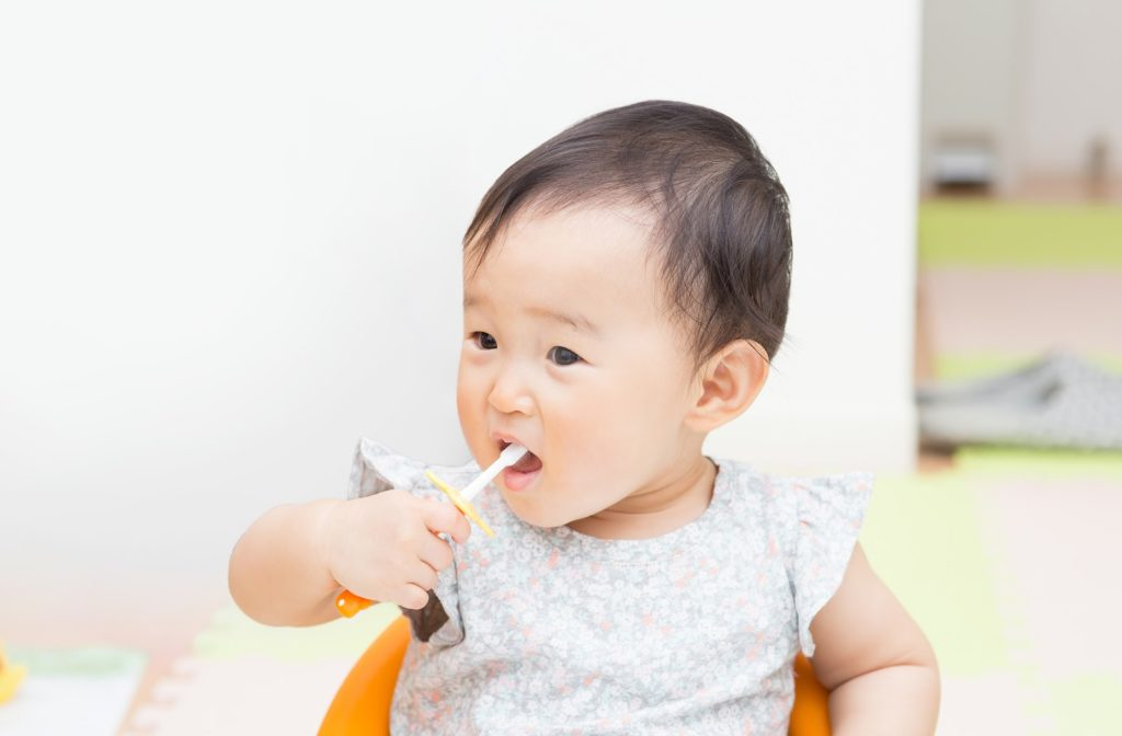Cute baby using toothbrush to clean teeth safely