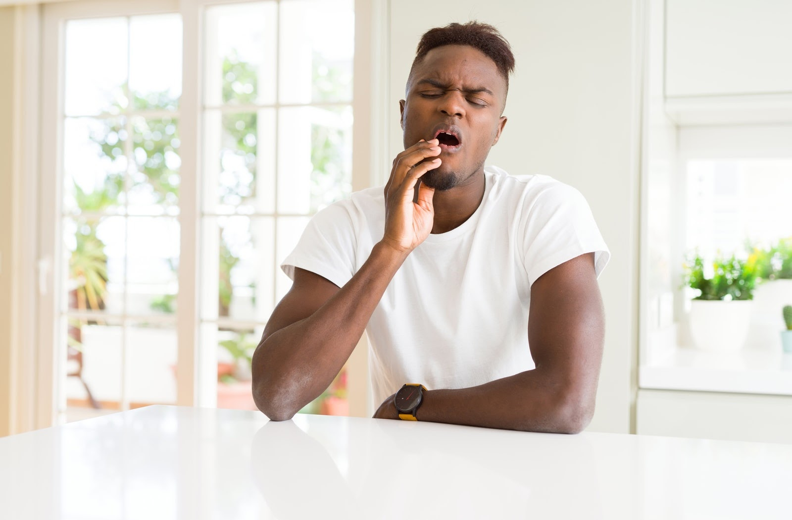 Man sitting at home feeling pain caused by his wisdom tooth infection