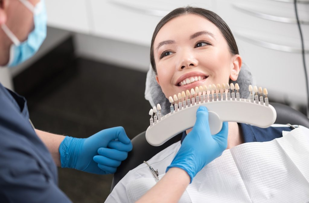 Dentist selecting dental crown while showing a smiling patient in a dental chair