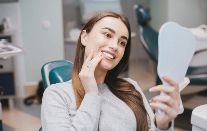 A woman sitting in a dentists chair looking at her newly whitened teeth